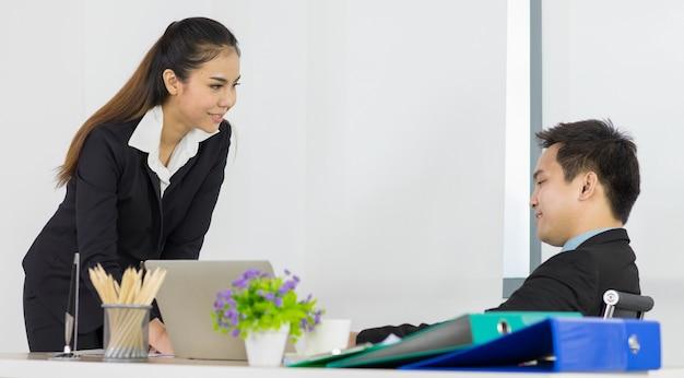 Paar aziatische kantoormensen vrouw en man medewerkers teamgenoot praten over werkplan zien er comfortabel en casual uit, voelen zich erg gelukkig op kantoor.