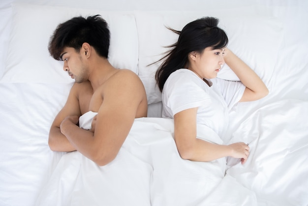 Paar aziatische man en vrouw op bed in witte slaapkamer