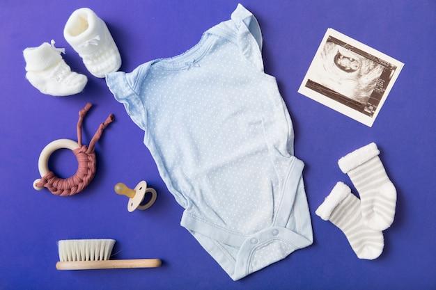 Paar babysokjes; wollen schoenen; fopspeen; speelgoed; baby onesie; penseel en echografie foto op blauwe achtergrond