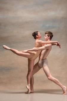 Paar balletdansers poseren over grijs.