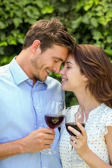 Paar bedrijf wijnglazen met ogen dicht aan voortuin