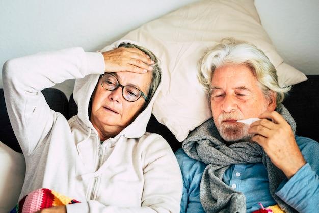 Paar bejaarde senioren thuis met seizoensgebonden winterkoude ziekte, gaan voor altijd samen op de bank zitten
