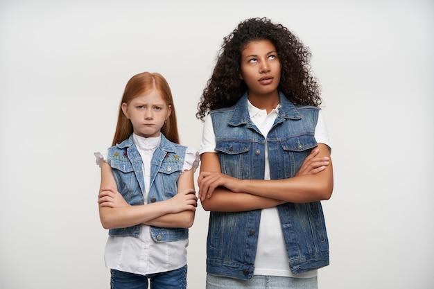 Paar beledigde jonge mooie meisjes poseren op wit, houden hun handen gevouwen en staan met ontevreden gezichten, hebben ruzie en willen niet met elkaar praten
