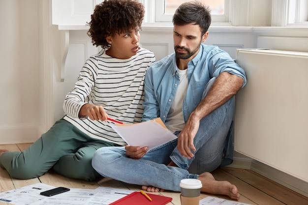 Paar berekenen hun rekeningen thuis, kijken wanhopig naar papieren, hebben veel onbetaalde belastingen, controleren documentatie, poseren op de vloer, drinken koffie halen uit een wegwerpbeker, denken aan het repareren van flat