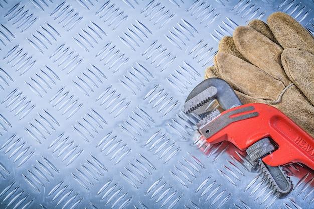 Paar beschermende handschoenenpijptang op gecanneleerd de bouwconcept van het metaalblad