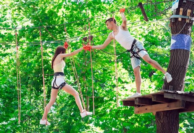 Paar besteden hun vrije tijd in een touwenparcours. man en vrouw die zich bezighouden met bergbeklimmen,