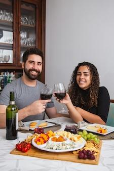 Paar bij romantisch diner dat wijn en kaas proeft. koppel met wijn- en kaassnacks in de winter. verticaal