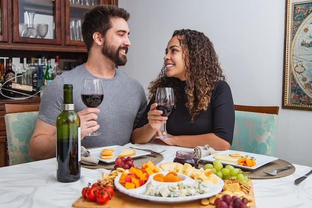 Paar bij romantisch diner dat wijn en kaas proeft. koppel met wijn- en kaassnacks in de winter