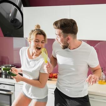 Paar binnenshuis gek rond in de keuken met garde