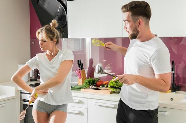 Paar binnenshuis gek rond in de keuken