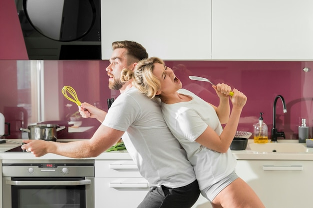 Paar binnenshuis zingen in de keuken zitten zijdelings
