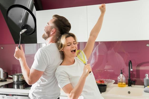 Paar binnenshuis zingen in de keuken