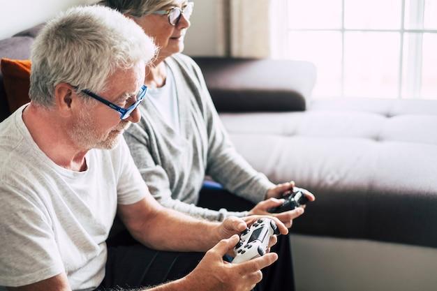 Paar blanke gepensioneerde senioren die samen videogames spelen thuis zittend op de bank - volwassen vrouw en man getrouwd - twee verloven voor altijd - met een controller of een joystick