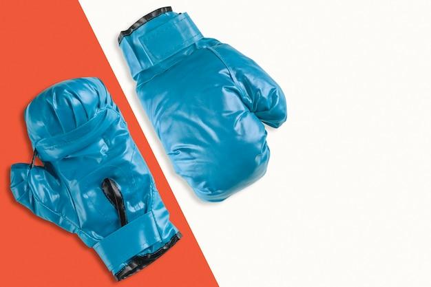 Paar blauwe bokshandschoenen op oranje en witte achtergrond
