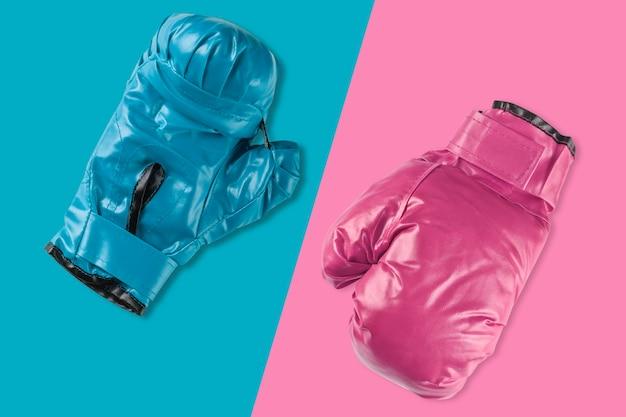 Paar blauwe en roze bokshandschoenen op blauwe en roze achtergrond