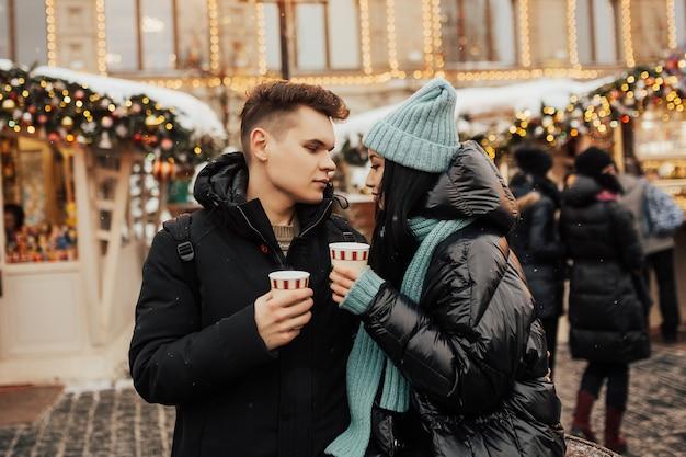 Paar brengt samen tijd door op de kerstmarkt met warme dranken