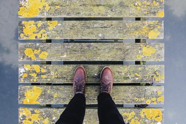 Paar bruine leerschoenen die zich op een oude grijze en gele brug bevinden