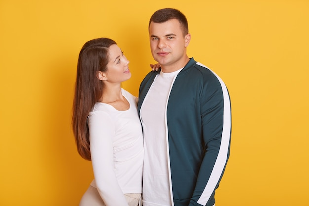 Paar, charmante vrouw glimlachend en kijken naar haar vriendje, knappe man direct kijken naar de camera