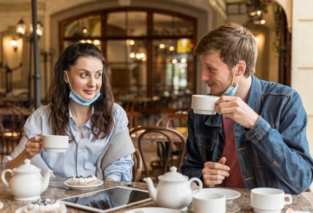 Paar chatten in het restaurant terwijl ze medische maskers op hun kin hebben