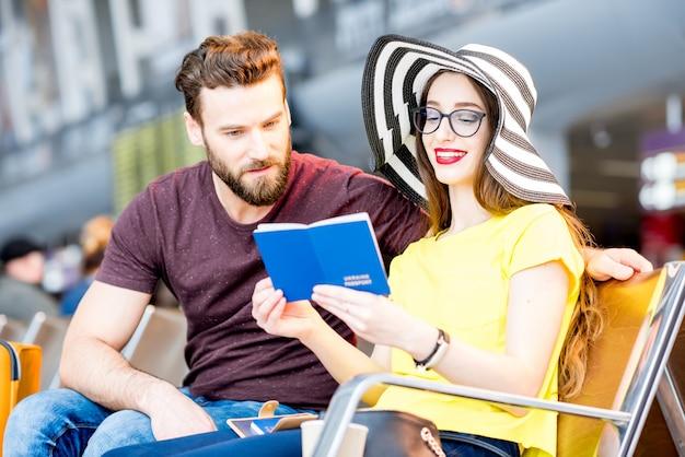 Paar controleren paspoorten zittend in de wachtkamer van de luchthaven tijdens hun zomervakantie