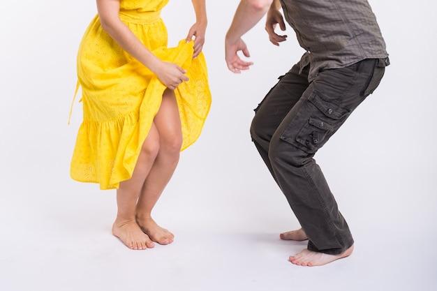 Paar dansen latijns-muziek. bachata, merengue, salsa en kizomba. close-up van de benen elegantie poseren op witte kamer.