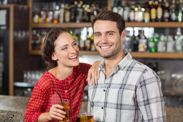 Paar dat bij camera glimlacht en bieren houdt