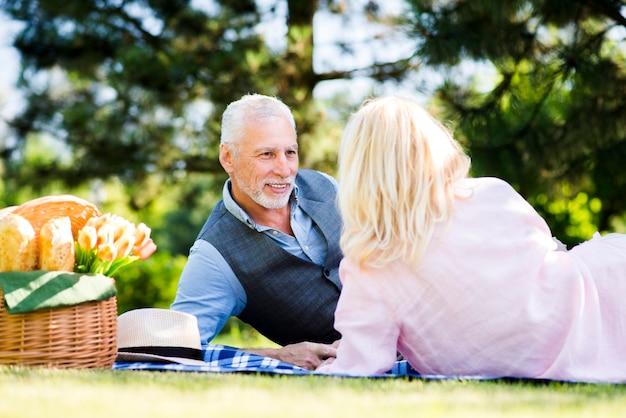 Paar dat bij een picknick in aard legt
