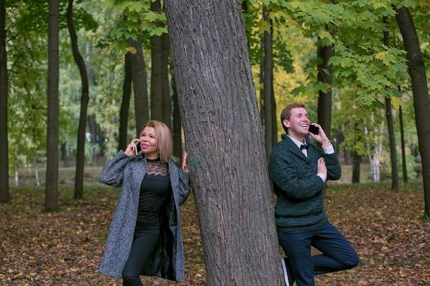 Paar dat bij hun mobiele telefoon gebruikt terwijl op een datum openlucht