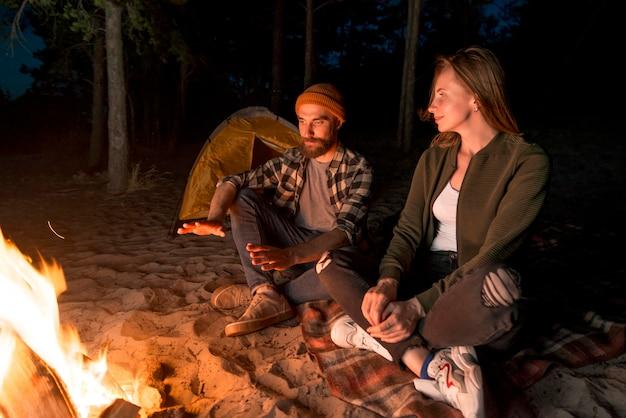 Paar dat bij nacht door een kampvuur opwarmt