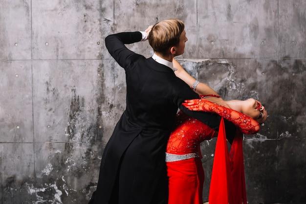Paar dat dichtbij grijze muur danst