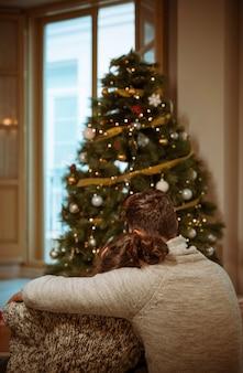 Paar dat dichtbij kerstboom koestert