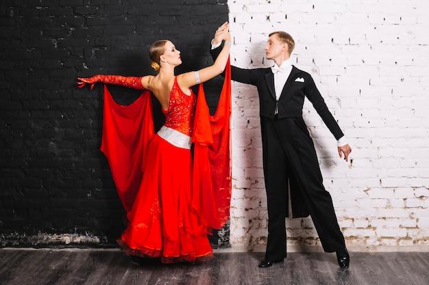 Paar dat dichtbij zwart-witte muur danst