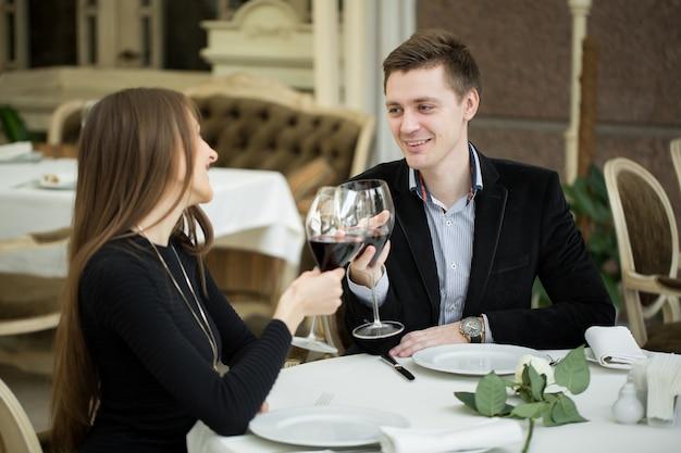 Paar dat diner heeft bij een restaurant en een toost maakt