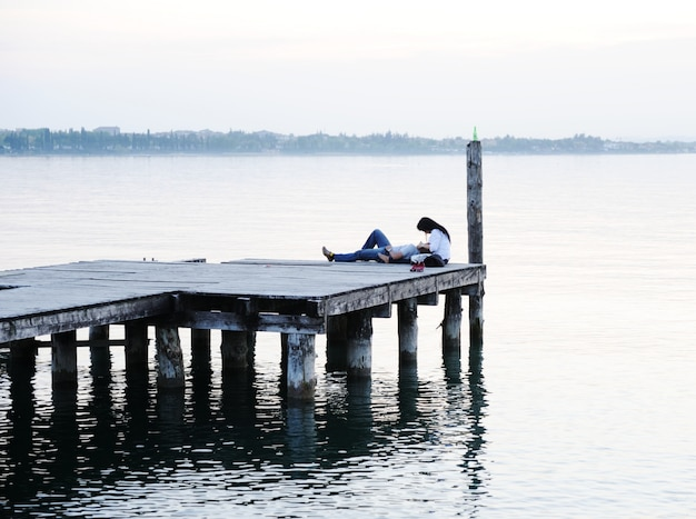 Paar dat door het houten dok op een mooi meer ligt