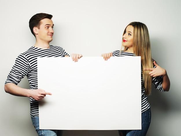 Paar dat een banner houdt - die over een witte achtergrond wordt geïsoleerd