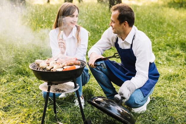 Paar dat een barbecue in aard doet