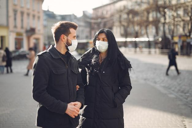 Paar dat een beschermend masker draagt dat zich op de straat bevindt