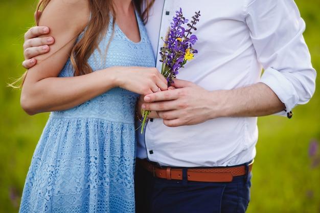 Paar dat een boeket van purpere bloemen houdt