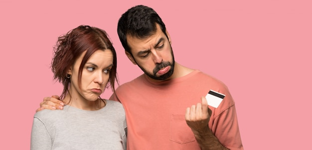 Paar dat een creditcard zonder geld over geïsoleerde roze achtergrond neemt