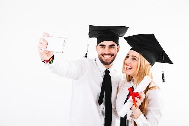 Paar dat een diploma behaalt en selfie neemt