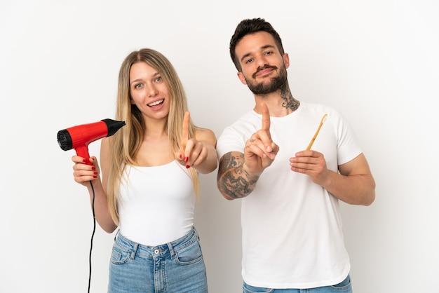Paar dat een haardroger vasthoudt en tanden poetst over een geïsoleerde witte achtergrond die een vinger laat zien en optilt