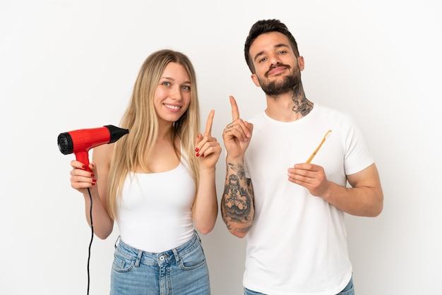 Paar dat een haardroger vasthoudt en tanden poetst over een geïsoleerde witte achtergrond die een vinger toont en optilt als teken van het beste