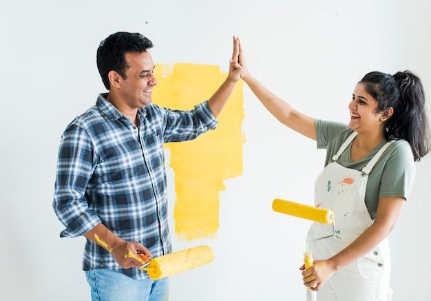 Paar dat een hoogte vijf geeft terwijl het vernieuwen van hun nieuw huis
