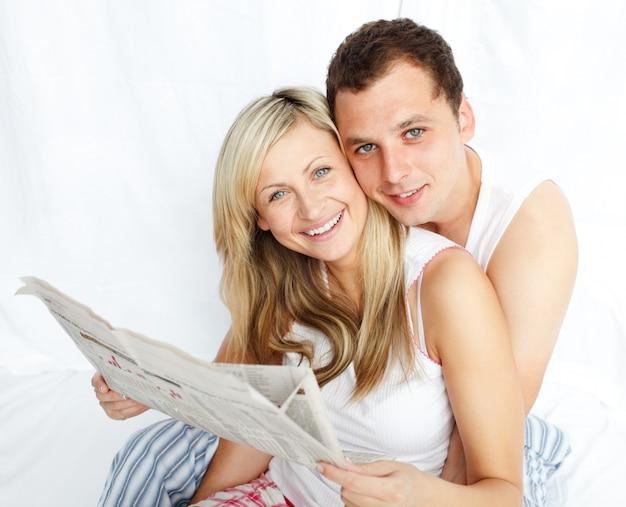 Paar dat een krant in bed leest en bij de camera glimlacht