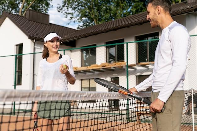 Paar dat een onderbreking op tennisbaan neemt