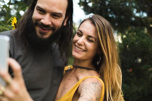 Paar dat een selfie met zonnebloemen neemt
