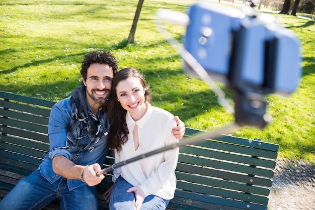 Paar dat een selfiestok in een park gebruikt