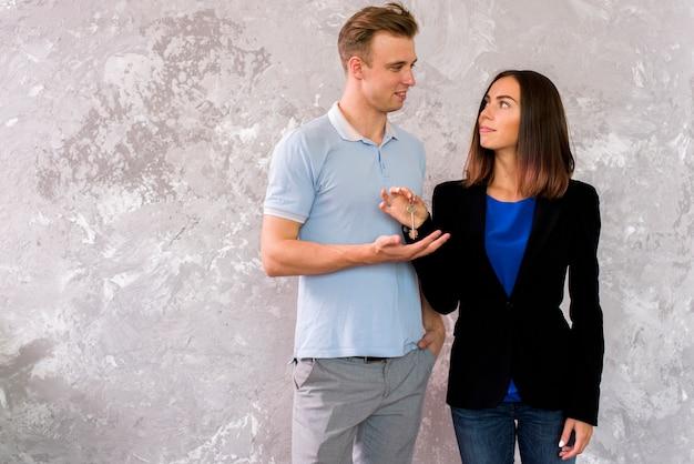 Paar dat elkaar bekijkt terwijl het houden van een reeks sleutels