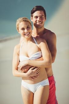 Paar dat elkaar op strand omhelst