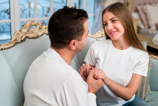 Paar dat en handen op bank glimlacht houdt
